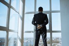 A Man in Suite at the Window. Handsome man standing next to the window, looking out. Bearded attractive gentleman in an elegant stylish clothes thinking. Back stock photography
