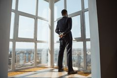 A Man in Suite at the Window. Handsome man standing next to the window, looking out. Bearded attractive gentleman in an elegant stylish clothes thinking. Back stock photo