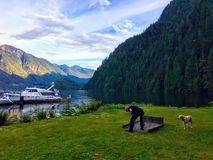 A man on summer boating trip, walking his dog and playing horseshoes, in the beautiful remote location of Indian Arm stock photos