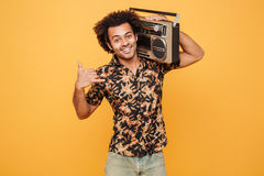 Man in summer clothes holding boombox on his shoulder. Portrait of a smiling african man in summer clothes holding boombox on his shoulder isolated over yellow Stock Photos