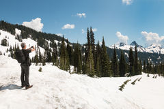 Man in summer clothes stand on snow. And takes pictures of mountain peaks Stock Photo