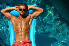 Man Summer Fashion. Male Model Tanning By Pool. Skin Tan. Man Summer Fashion. Beautiful Male With Sexy Body In Swimwear, Fashionable Sunglasses Tanning, Floating Stock Image