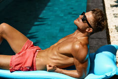 Man Summer Fashion. Male Model Tanning By Pool. Skin Tan Stock Photo