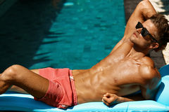 Man Summer Fashion. Male Model Tanning By Pool. Skin Tan. Man Summer Fashion. Beautiful Sexy Male With Fit Body In Swimwear, Fashionable Sunglasses Tanning By Stock Images