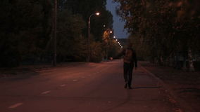 Man in summer night, with a backpack goes on road stock video
