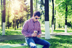 The man in the summer in the park, relaxing with a cup of coffee or tea, reading  sms on phone wearing glasses,  news Royalty Free Stock Images