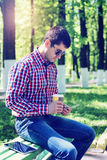The man in the summer in the park, relaxing with a cup of coffee or tea, reading  sms on phone wearing glasses,  news Stock Photo