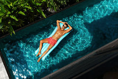 Man On Summer Vacation. Male Model Tanning In Swimming Pool Royalty Free Stock Photography