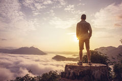 Man On A Summit Above The Clouds. Man standing on top of a mountain above the clouds with the sun rising in front of him Royalty Free Stock Photography