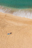 Man sun bathing solo on secluded beach Royalty Free Stock Images