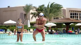 Man in sun glasses, father and daughter, kid girl, dancing in the pool water, having fun together. Happy family relaxing