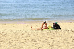 A man sunbathe at the beach and touch the mobile, Pattaya Thailand. A man sunbathe at the beach and touch the mobile, Pattaya Thailand, as nature background Stock Image