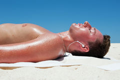 Man sunbathes and listens to music on the beautiful beach Stock Photos