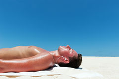 Man sunbathes and listens to music on the beautiful beach Stock Photo