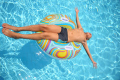 Man sunbathes lying on an inflatable toy Stock Photo