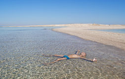 Man sunbathes lying in the water. Leisure, pleasure. Egypt, Red Sea. Sand, deserted island. A man sunbathes lying in the water Royalty Free Stock Images