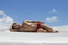 Man sunbathing on the beach. With blue sky Royalty Free Stock Images