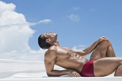 Man sunbathing on the beach. Profile of man sunbathing on the beach Stock Photography