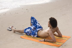 Man Sunbathing at the Beach. Young Man Sunbathing at the Beach stock image