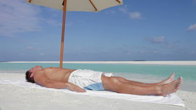 Man Sunbathing On Beach Holiday. Man lying on towel under parasol before sitting up to look at view.Shot on Canon 5d Mk2 with a frame rate of 30fps stock video
