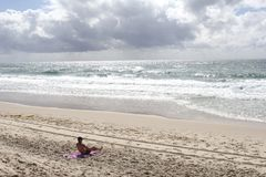 Lonely man at a desolated white sandy beach along the ocean,Gold Coast, Australia Royalty Free Stock Photography