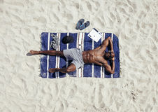 Man sunbathing on the beach Stock Photography
