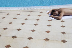 A man sunbathing by a pool Stock Photography