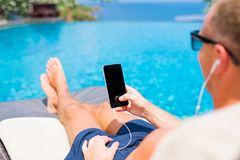 Man sunbathing by the pool and holding mobile phone in hand. Young man sunbathing by the pool and holding mobile phone in hand royalty free stock photo