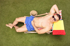 Man sunbathing in a sun lounger in his backyard Stock Images