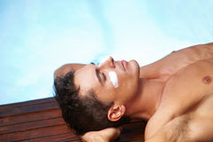 Man sunbathing with sunscreen on face Stock Images