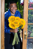 Man with sunflowers. A young African American man standing at a patio door, carrying a bunch of large sunflowers Stock Photo