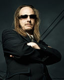 Man in Sunglasses with Arms Crossed. Low perspective shot of a long-haired, balding man standing with his arms crossed Stock Images