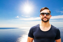 Man with sunglasses. Athletic man with sunglasses on the sea Stock Photography