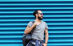 Man in sunglasses with bag standing at street wall Royalty Free Stock Photography