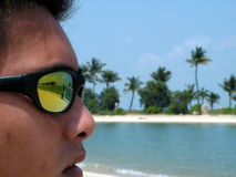 Man with sunglasses at beach. Resort living with sun tanning. A man with suntanned face and sunglasses looking into distance, reflection of people on the beach Royalty Free Stock Photo