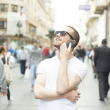 Man with sunglasses and cell phone on street Stock Image