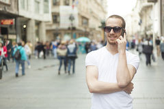 Man with sunglasses and cell phone walking Stock Photography