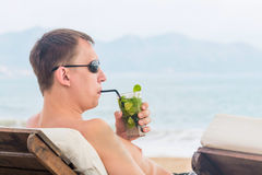 Man in a sunglasses drink a cocktail. Close up portrait of young man in a sunglasses drink a cocktail mojito, on the blue sky and ocean background stock image