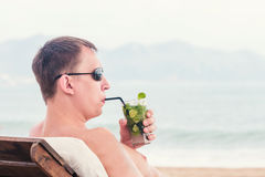 Man in a sunglasses drink a cocktail. Close up portrait of young man in a sunglasses drink a cocktail mojito, on the blue sky and ocean background stock photos