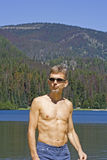 Man with sunglasses in front of a lake and mountains. Manning provincial park, canada - adobe RGB Royalty Free Stock Photography