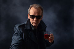 Man in sunglasses with glass of whiskey Royalty Free Stock Photo