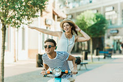 Man in sunglasses and happy young woman in straw hat riding moped and smiling. Handsome men in sunglasses and happy young women in straw hat riding moped and Stock Photos