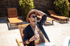Man in sunglasses and hat drinking beer, sitting on chaise. Young handsome man in sunglasses and hat drinking beer, sitting on chaise. Copy space stock photo
