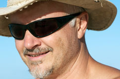 Man with sunglasses and hat. Headshot portrait of handsome mature man with dark sunglasses and cowboy hat; pepper and salt goatie and stubble Royalty Free Stock Image