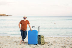 Man in sunglasses and hat with luggage on the sea in summer sunny day Stock Photo