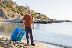 Man in sunglasses and hat with luggage on the sea in summer sunny day Stock Image