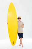 Man in sunglasses and hat showing thumbs up holding surfboard Stock Photo