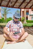 Man in sunglasses and a hat sitting on a a lounger and plays in the smartphone Royalty Free Stock Photos