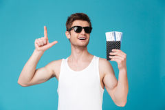 Man in sunglasses holding pasport with tickets Royalty Free Stock Photography
