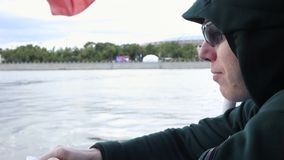 Man in sunglasses, hood, eats seeds, spits out, sails on river in boat. water transport trip. waving russian flag stock footage
